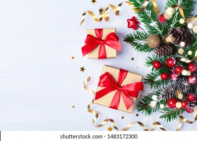 Two golden gift or present boxes, snowy fir branches, conifer cones, Christmas decoration and red berry on white table top view