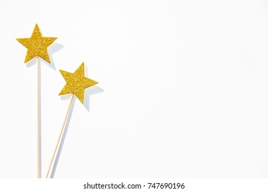 Two golden party magic wands on a white background. Copy space.