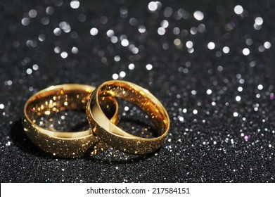 Two golden rings on black glitter background