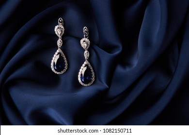 Two Golden sapphire earrings with small diamonds. Pair of platinum earring with sapphire gemstone on blue satin background. Luxury female jewelry, close-up