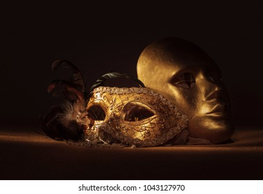 Two golden Venetian masks , focus on foreground.