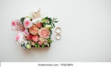 Two golden wedding rings arranged near beautiful and cute flower composition in a little box on the white background. Top view