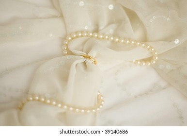 Two golden wedding rings on a bridal veil