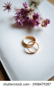 Two golden wedding rings and pink flowers on white background. Vertically framed shot.