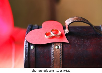 Two golden wedding rings with a red heart on beautiful wooden vintage box.