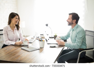 Two good looking workers sitting in an office, drinking coffee and smiling at each other