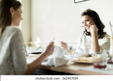 Two gorgeaus ladies eating in a restaurant while having a conversation