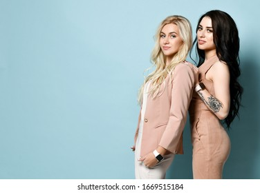 Two gorgeous females with long curly hair, in fashion clothes, watches, high heels. They smiling, posing standing sideways against blue studio background. Beauty and fashion. Copy space. Close-up