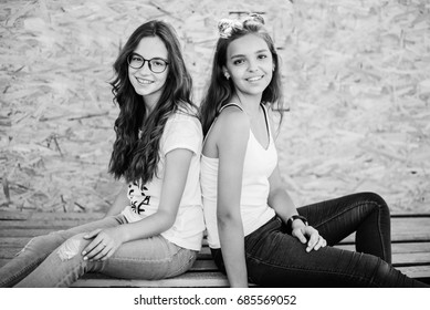 Two gorgeous girls sitting on wooden bars against veneer wall. Black and white photo.