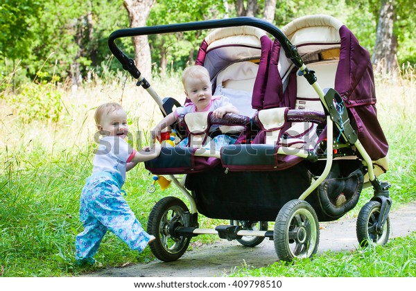 Two gorgeous girls twins walking on green grass with pleasure on a double buggy