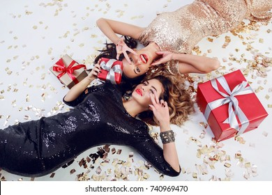 Two gorgeous  seductive woman in trendy sequin dress lying on white floor with shining golden confetti and red gift boxes . Celebrating new year or birthday party. Showing peace.