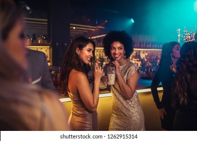Two gorgeous young women enjoying cocktails