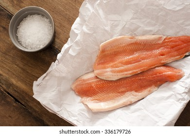Two gourmet raw rainbow trout fillets lying on crumpled white paper with a ramekin of rock salt alongside waiting to be cooked, overhead view