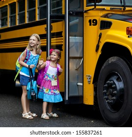 Two grade school girls getting on school bus for first day of school.