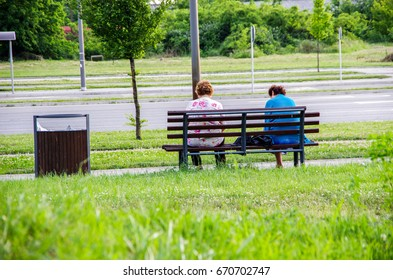 Two grandmas sitting on the bench and enjoying their retirement. Holiday.