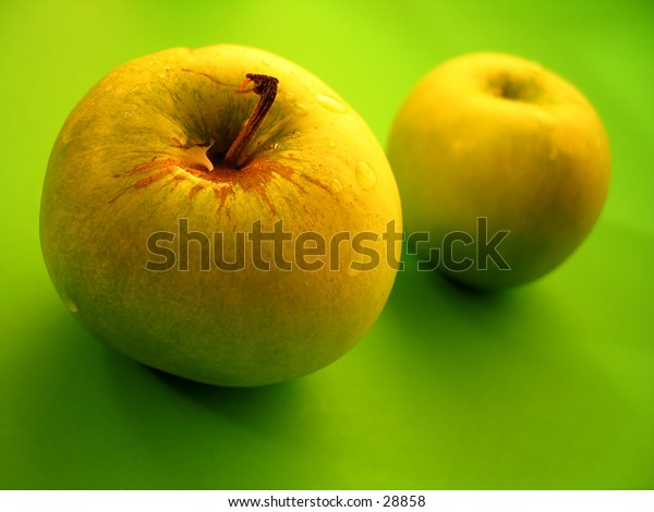 Two grannysmith green apples, focus on the front apple.