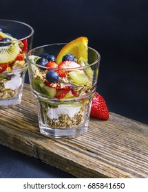 Two granola desserts with fresh fruits on a wooden board
