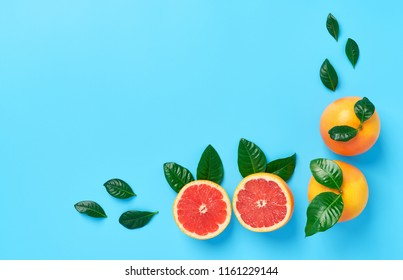 Two grapefruit with  green leaf and ripe half of pink grapefruit on a blue background.top view