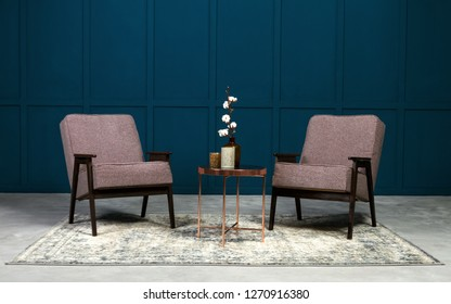 Two gray armchair and copper coffee table and vases on it in blue room