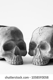 Two gray concrete human skulls on white background. A skull made of cement for home decor