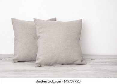 Two gray cushions on the wooden table side view. Soft square pillows on a wooden surface against the white background.