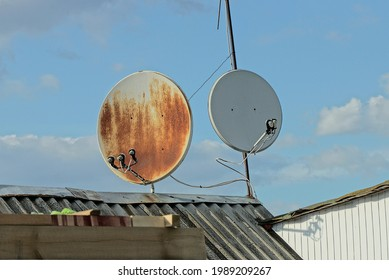 two gray round satellite dishes in brown rust on the slate roof of a private house against a blue sky