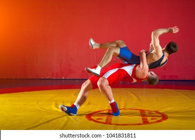 Two greco-roman  wrestlers in red and blue uniform wrestling  on background on a yellow wrestling carpet in the gym