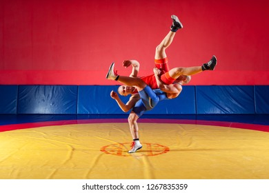 Two greco-roman  wrestlers in red and blue uniform making a suplex wrestling   on a yellow wrestling carpet in the gym. The concept of fair wrestling
