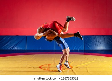 Two greco-roman  wrestlers in red and blue uniform wrestling  on background on a yellow wrestling carpet in the gym. The concept of fair wrestling