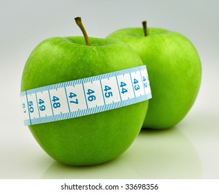 two green apple with measuring tape