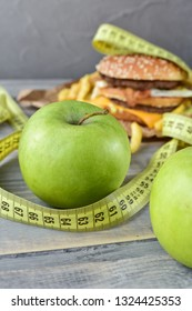 two green apples on the background of a burger and fries. Sewing Tape Measures lies on the food. concept of opposition  healthy food and junk food. selective focus