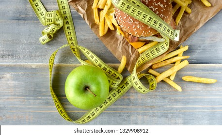 two green apples on the background of a burger and fries. Sewing Tape Measures on the food. concept of opposition  healthy food and junk food. selective focus