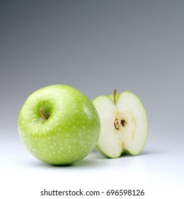 Two green apples one is full and the other one is half on a white background