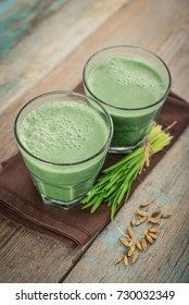 Two green barley grass shots with blades of young barley on a wooden background
