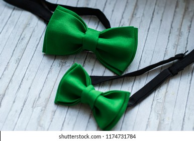 Two green bowties on a wooden background. Accessory for formal dress.  Family look. Вow tie for father and son.