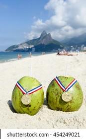 885f3d44be2 Two green Brazilian coco gelado drinking coconuts wear gold medals on Ipanema  Beach in Rio de
