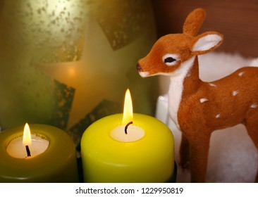two green candles with a bambi in the snow