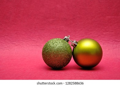 Two green Christmas tree baubles on a pink background