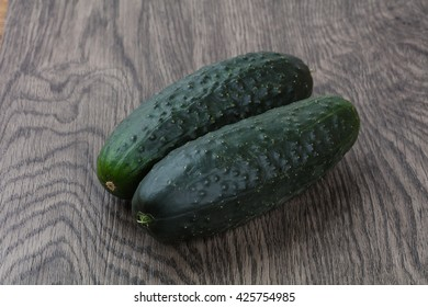 Two Green cucumbers on the wood background