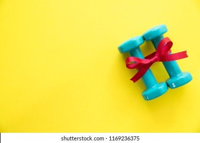 two green dumbbell with red gift bow on a yellow table background, sport and healthy concept