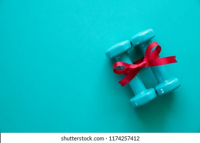 two green dumbbell with red gift bow on a green table background, sport and healthy concept