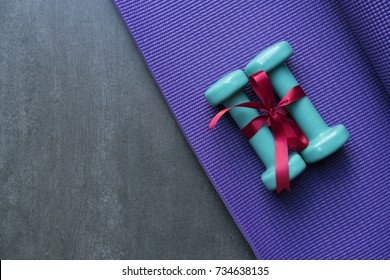 two green dumbbell with red gift bow on a yoga mat background, sport and healthy concept
