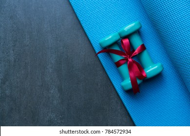 two green dumbbell with red gift bow on blue yoga mat background, sport and healthy concept
