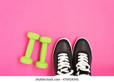 Two green dumbbells and black sneakers over pink background, top view