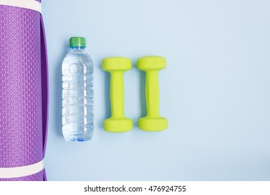 Two green dumbbells, bottle of water and yoga mat over blue background
