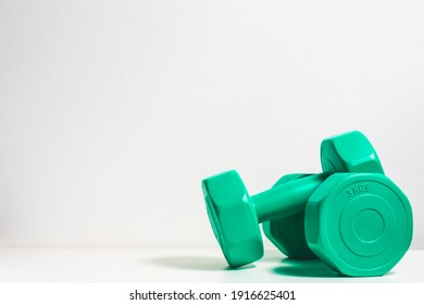 Two green dumbbells on the white table isolated on white background with copy space.