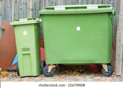 Two green garbage bins with junk behind, Both are closed and have wheels for easier transport. One is big and the other small.