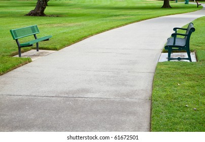 Two green metal benches across a large concrete pathway in a park