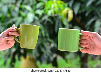 Two green mugs held high together with green nature background.