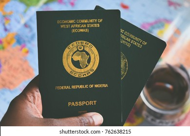 Two green Ngerian Passports in African dark brown skin hand with atlas and travel jar naira in background
